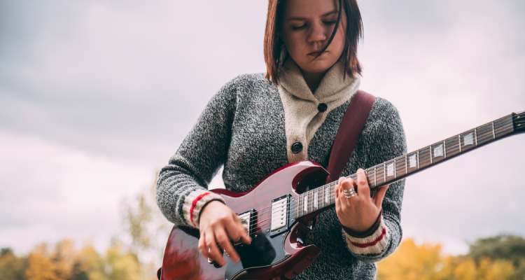 female playing the guitar